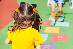 Kids play hopscotch on the school
