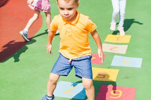 Boy jumps by playing hopscotch
