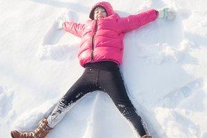 Girl makes snow angel
