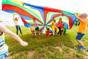 Happy kids waving rainbow parachute