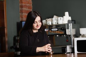 Woman barista use the coffee tamper