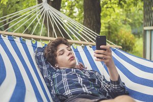 close up young man using phone lying