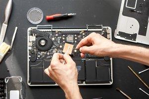 overhead hands repairing laptop hard