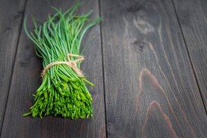bunch of fresh chives on a wooden cu