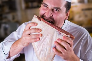 Chef biting raw meat on the kitchen