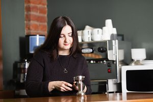 Woman barista use tamper