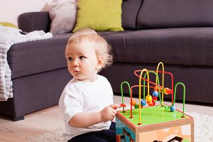 Infant baby boy playing indoors with