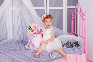 Baby girl sitting on her bed wearing
