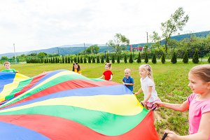 Rainbow parachute held by children
