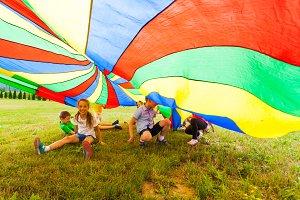 Happy kids hiding under colorful