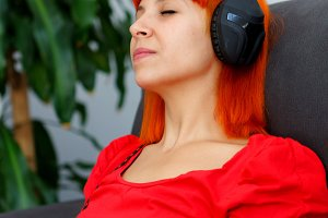 Relaxed woman in red listening music
