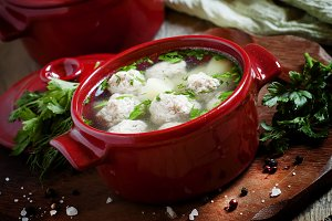 Soup with meatballs in red pots, sel