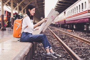 Girl wearing backpack holding map, w