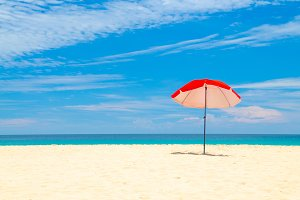 red umbrella beach white sand and bl