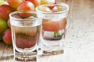 Grappa in a small glass and ripe gra