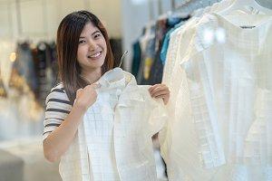 Happy Asian woman choosing clothes i