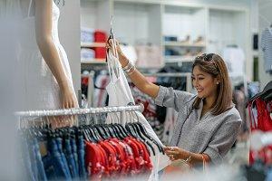 Happy Asian woman choosing clothes w