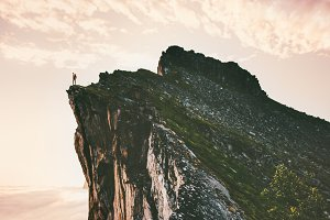 Man standing on cliff edge mountain