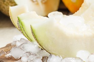 Fresh melon with ice on a wooden boa