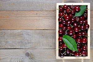 Cherry in wooden box on table