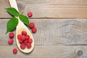 Raspberry in spoon on wooden table
