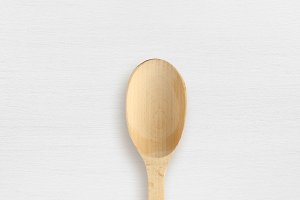 Empty wooden spoon on white table