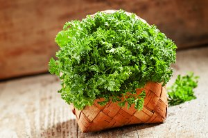 Fresh curly parsley on an old wooden