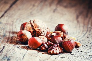 Hazelnuts and walnuts on old wooden