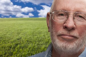 Melancholy Senior Man with Grass Fie
