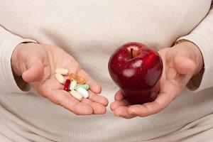 Senior Woman Holding Pills and Apple
