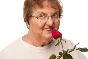 Attractive Senior Woman with Red Ros