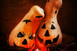 Two Halloween pumpkins on a dark bac