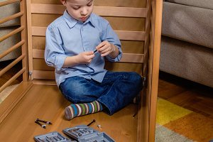 Kid with tools assembling furniture