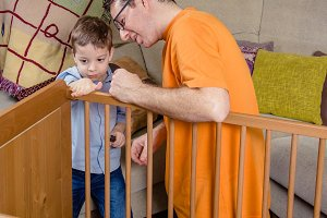 Father and son assembling baby cot
