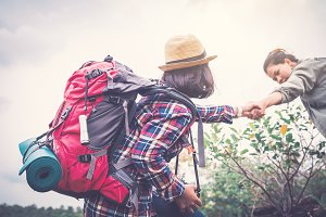Women helping partner backpacker
