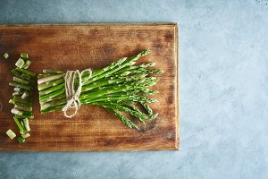 bunch of asparagus on wooden cutting