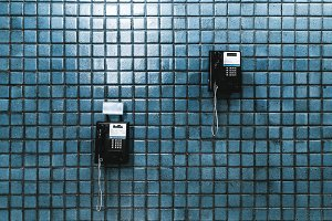 Two public telephones on tiled wall