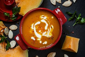 Pumpkin soup with sour cream in a sa
