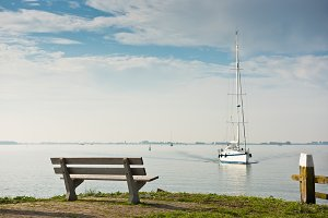 Scenic sea view with bench and sailb