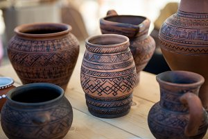 There are many clay pots on the tabl