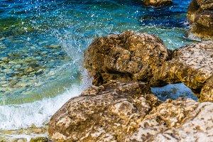 Wave crashes onto rocks on sunny day