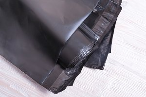 Black polythene envelope on wooden d