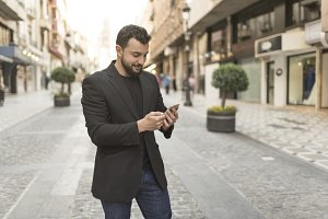 Man in street looking smartphone