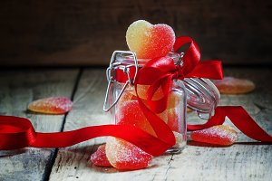 Fruit jelly hearts in a glass jar, t