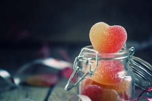 Fruit jelly hearts in a glass jar wi