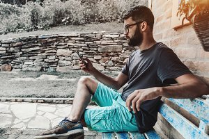 Bearded hipster in glasses texting