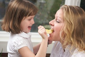 Daughter Feeding Mom an Apple