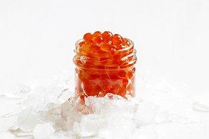Red salmon caviar in a glass jar on