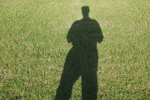 man shadow over green meadow