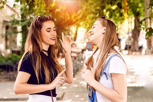 two girlfriends dance while listenin